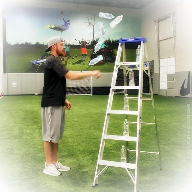 Dude Perfect's Garrett Hilbert flips water bottles onto step ladder