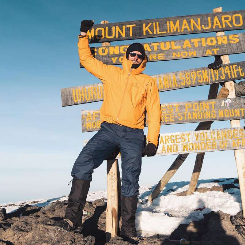 Erik Conover poses atop the summit of Mount Kilimanjaro
