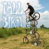 One of the Zenga Bros rides his tall bike on a grassy field